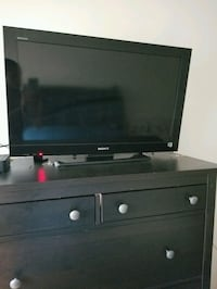 black flat screen TV with brown wooden TV stand Takoma Park, 20912
