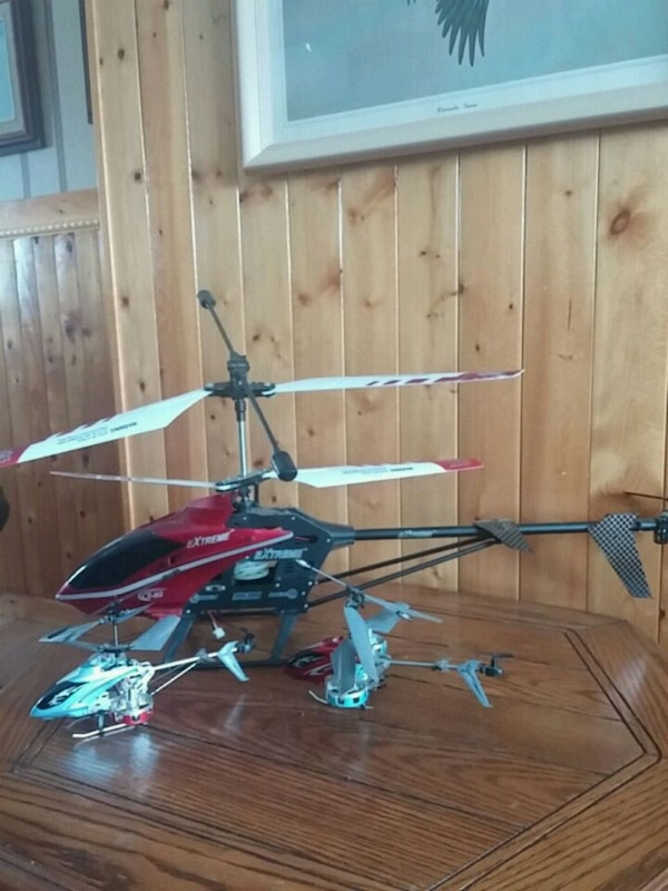 three assorted colors of RC helicopters