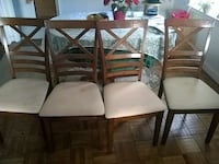 four brown wooden framed white padded chairs