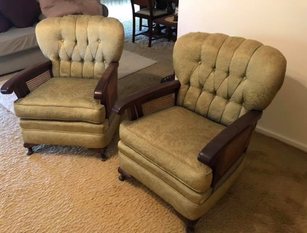 Two brown wooden framed light green padded armchairs and couch