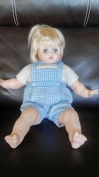 doll wearing white and blue gingham overalls