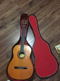 brown wooden classical guitar with red and black hard case