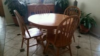 round brown wooden table with four chairs dining s