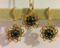 three gold-colored green gemstone necklaces