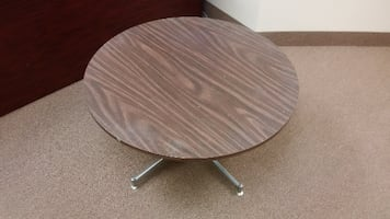 Round brown wooden pedestal table for office or home