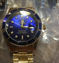 round blue Rolex analog watch with gold link bracelet