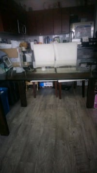 Dining Table with glass top and black wood feet. C Surrey, V3R 0B3