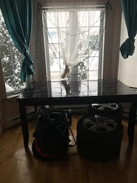 black wooden table; silver-colored 5-spokes automotive wheel set ; white and teal window curtains Laval, H7R 6G1