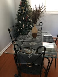 Wrought iron dark green dining table with 4 chairs.  Glass top. Toronto, M4A 1X1