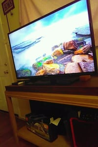 black flat screen TV with brown wooden TV stand San Antonio, 78242