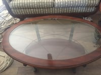 oval brown wooden framed glass top coffee table