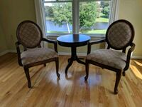 two brown wooden framed padded armchairs Frederick