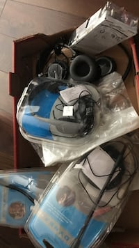 Blue and black corded headphones in box and few computer microphones