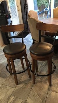 two brown wood-framed black leather padded bar stools