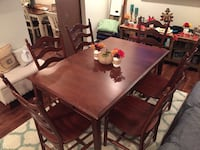 Rectangular brown wooden table with six ladder-back chairs dining set
