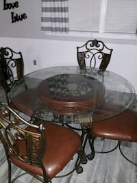 round clear glass-top table with black steel base 835 mi