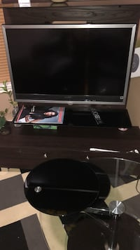 black flat screen TV with black wooden TV stand Surrey, V3W