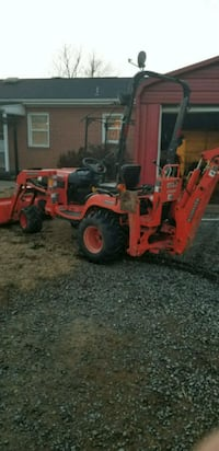 red and black tractor with plow blade 39 mi
