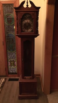 brown wooden grandfather's pendulum clock