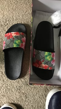 pair of black, gray, and green Gucci floral slide sandals