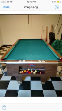 Pool table (slate)with cue sticks and balls.