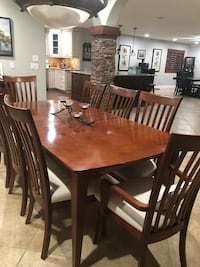 Rectangular brown wooden table with eight chairs, dining set, china cabinet, and buffet