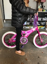 Pink and black bicycle with training wheels