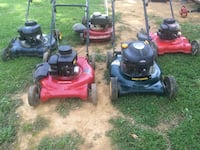 Five red, black, and blue push mowers 59 km