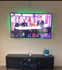 flat screen television with black wooden TV stand Houston, 77002