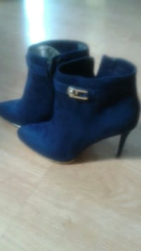 pair of blue suede heeled bcukled boots