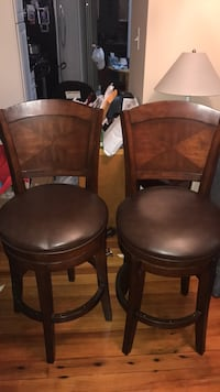 Two brown wooden framed black leather padded chairs Seekonk, 02771