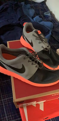 pair of grey and neon orange running shoes size 10 1/2 253 km