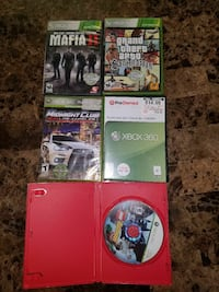 red Xbox 360 console with controller and game case
