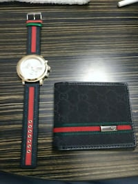 round silver analog watch with red leather strap