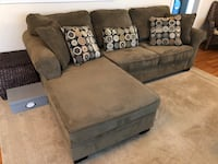 Green couch with chaise and pillows