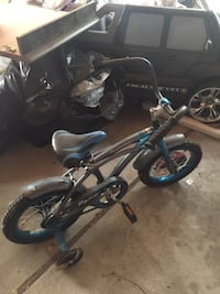toddler's black and blue bike with training wheels
