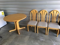 three brown wooden framed gray padded armless chairs