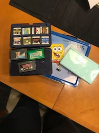 Green nintendo ds with game cartridges