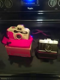 two white and silver point-and-shoot cameras with two boxes