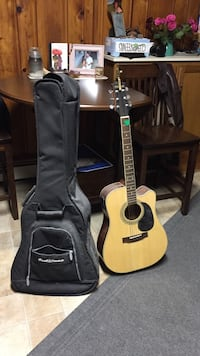brown and black acoustic guitar with bag