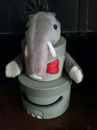 two round grey and red gift box with one grey and white elephant plush toy