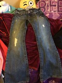pair of washed distressed blue flare jeans
