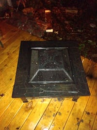 Like new outdoor fire pit has grate .