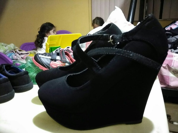 pair of black suede wedge shoes