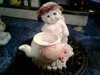 bare toddler's with floral headdress beside ceramic teapot decor