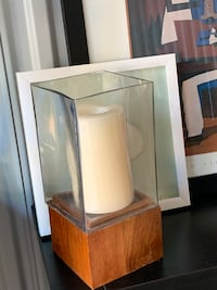 Large candle encased with glass box on base