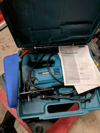 blue and black corded power tool in case
