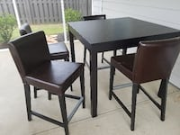 black square wooden table with four chairs null