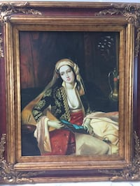 brown wood-framed painting of woman in black and beige clothing sitting on furniture