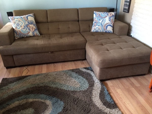 Brown fabric sectional sofa pulls out to a bed. Side lounger lifts up for  storage.